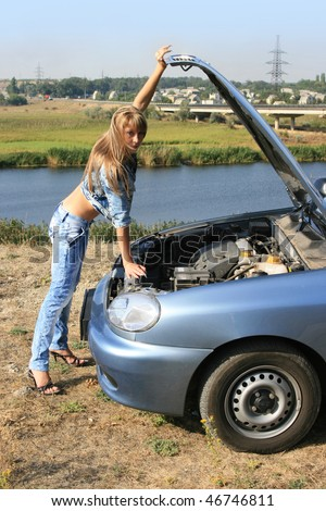 Blonde girl-mechanic standing near the car