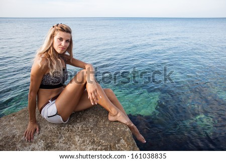 Blonde girl on rocky beach