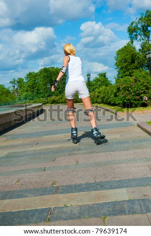 Blonde girl on roller skates rides in the park - stock photo