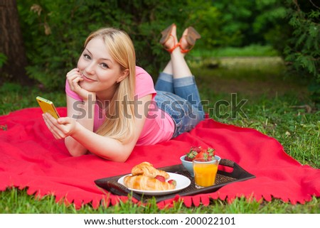 blonde girl outdoor in the park on picnic using her cell phone  - stock photo