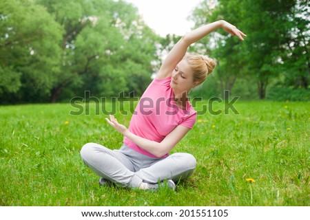 blonde girl outdoor in the park wearing grey shoes and pick t-shirt. yoga - stock photo