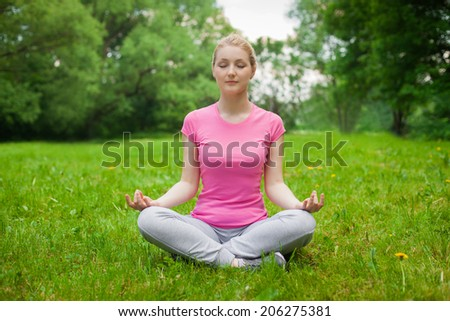 blonde girl outdoor in the park wearing grey shoes and pink t-shirt. yoga - stock photo