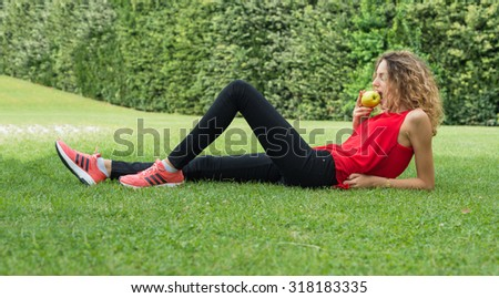 Blonde girl relaxing outdoor, eating apple during exercise. Diet and happiness concept. - stock photo