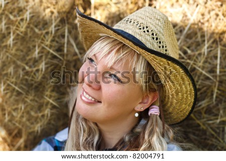 Blonde girl`s portrait in cowboy hat on straw bales background. - stock photo