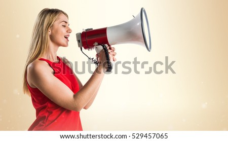 Blonde girl shouting by megaphone on ocher background