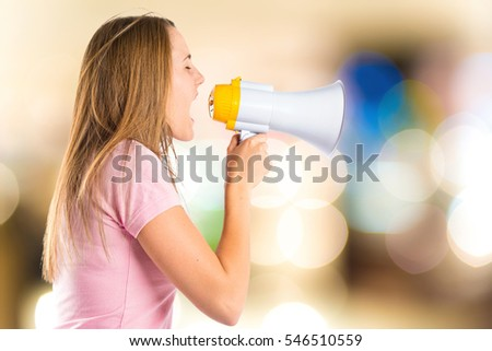 Blonde girl shouting with a megaphone on unfocused background