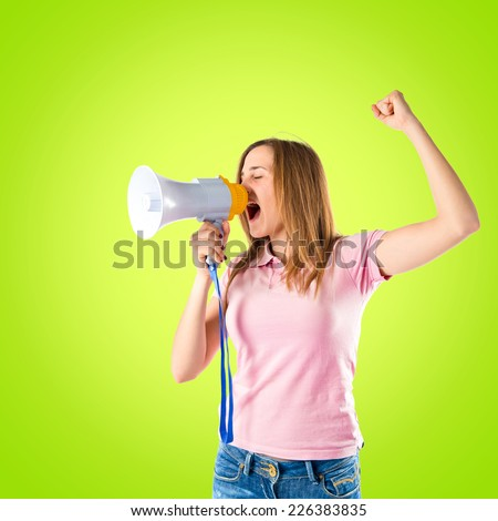 Blonde girl shouting with a megaphone over green background  - stock photo