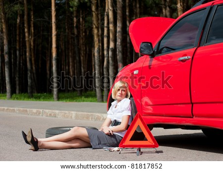 Blonde girl sitting near broken car and waiting for help - stock photo