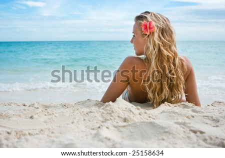 Blonde girl sitting on white sand on the beach