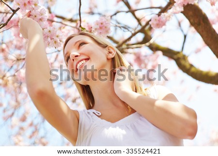Blonde girl standing at cherry blossom in a garden under a blooming tree