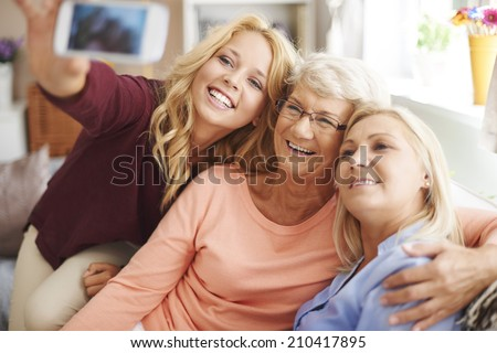 Blonde girl taking selfie with mom and grandma - stock photo