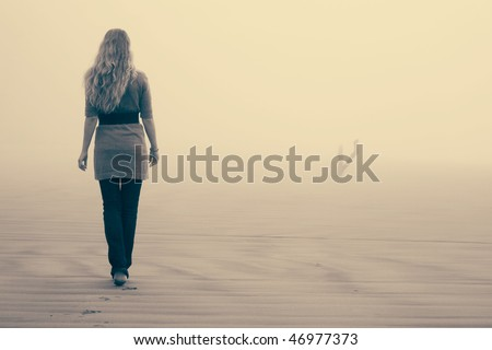 Blonde girl walking in the fog on the beach