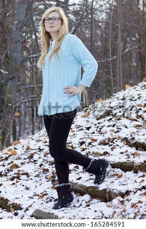 Blonde girl walking in the park at winter.