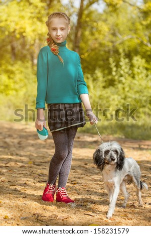 Blonde girl walking with pet in autumn garden