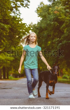 blonde girl walking with the dog or doberman in summer park. Warm toned photo