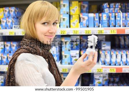 Blonde girl wearing scarf holds lamp in shop; shallow depth of field - stock photo