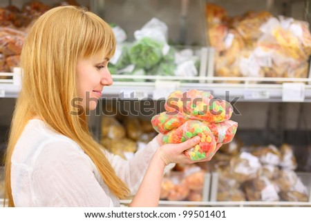 Blonde girl wearing white shirt holds colorful candied fruits in store; shallow depth of field - stock photo