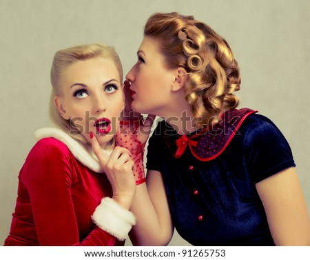 blonde girl whispers to her friend's ear - stock photo