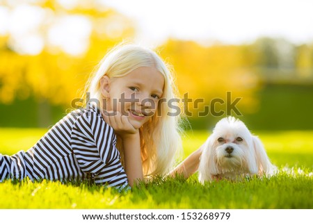 blonde girl with a dog lap dog. look in the picture. autumn landscape - stock photo
