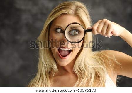 Blonde girl with a magnifying glass on smoky background