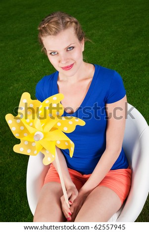 blonde girl with a pinwheel on a swivel chair - stock photo