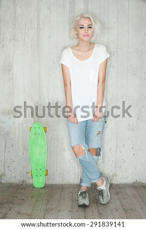 Blonde girl with a skate in a white T-shirt and jeans against a background of a cement wall - stock photo