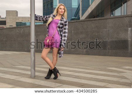Blonde girl with bag is leaning on post and looking to the left