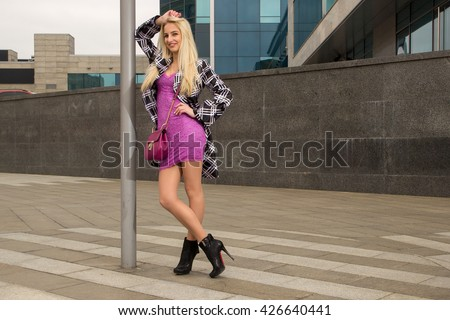 Blonde girl with bag is leaning on post and smiling