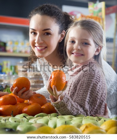 blonde girl with beautiful mother buying mandarins in shop. focus on girl