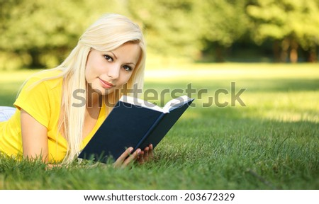 Blonde Girl with Book on Green Grass. Beautiful Woman Outdoor. Back to School. Portrait