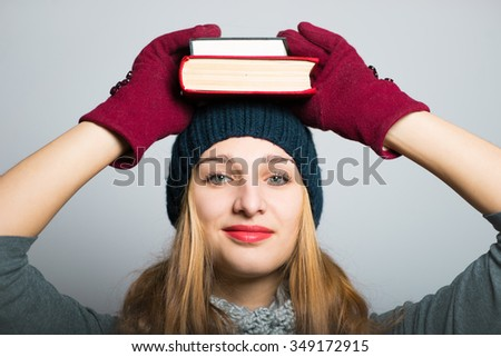 blonde girl with books on the head, Christmas and New Year concept, studio photo isolated on a gray background - stock photo