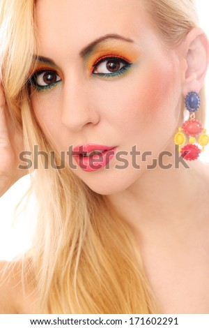 Blonde girl with earring has colored makeup - stock photo