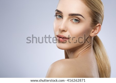 Blonde girl with fixed hair, blue big eyes, thick eyebrows and naked shoulders looking at camera at gray studio background, beauty photo, make up model, portrait. - stock photo
