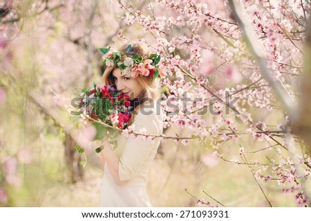 Blonde girl with flowers in pink peach garden. Beautiful girl outdoors spring portrait, young woman with flowers in green park spring concept. cheerful teenager walking outdoor. soft light style color - stock photo