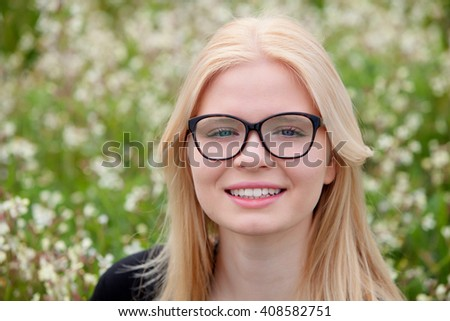 Blonde girl with glasses in the field surrounded by flowers