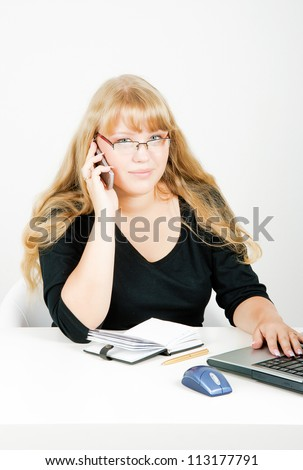 blonde girl with glasses talking on the phone in the office