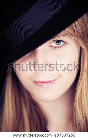 Blonde girl with hat looking at camera