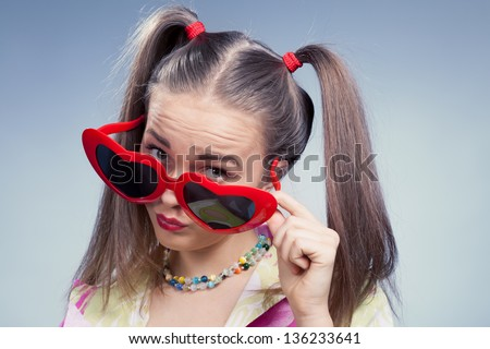 Blonde girl with heart glasses against blue background