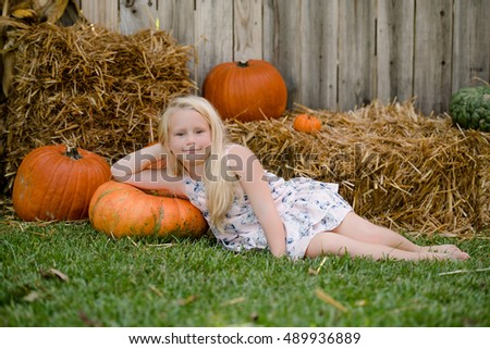 Blonde girl with long hair lying on the grass  by the hay with pumpkins fall decorations