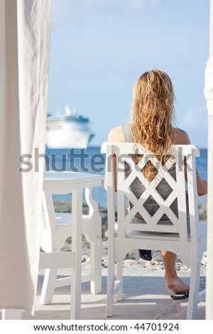 Blonde girl with long hair sitting on the white chair in front of the sea with cruise ship on background