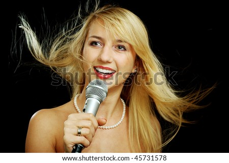 Blonde girl with naked shoulders singing in microphone, isolated on black