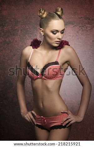 blonde girl with perfect body posing with creative hair-style, pink sensual lingerie and some red roses on the shoulders. Lovely fashion glamour portrait  - stock photo