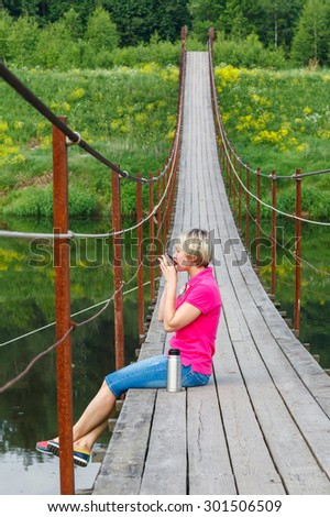blonde girl with short haircut drinking tea from a thermos on Pedestrian suspension bridge of steel and wood over the river, summer in Russia