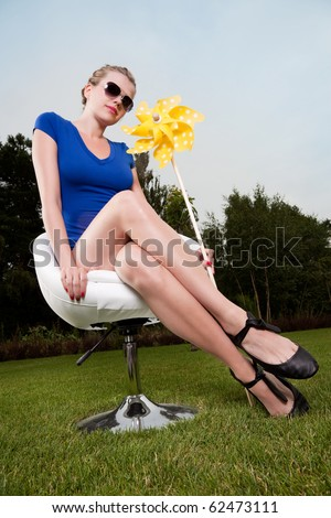blonde girl with sunglasses and a pinwheel on a swivel chair - stock photo