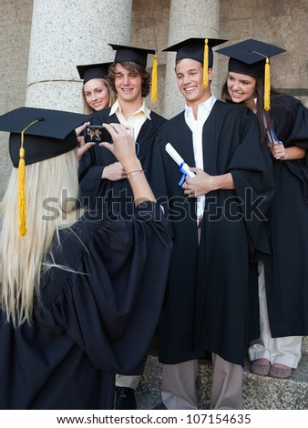 Blonde graduate taking a picture of her friend in front of the university - stock photo
