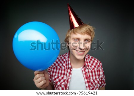 Blonde guy ready to let go of balloon smiling at camera celebrating fool�s day - stock photo