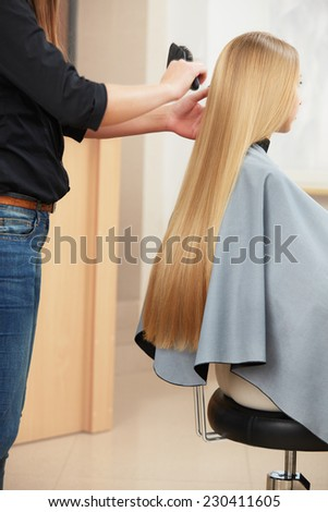 Blonde hair. Hairdresser combing long blonde hair in salon - stock photo