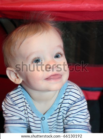 Blonde haired, blue eyed, caucasian baby boy with cute smiling facial expression sits in red tent with static hair standing on end - stock photo