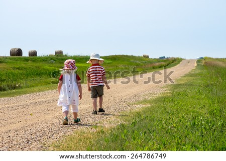 blonde haired brother & sister walking away down a country road - stock photo