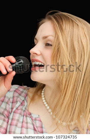 Blonde-haired woman singing against black background - stock photo